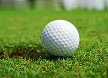 Golf ball at the hole. Ball view for the golf course with hole Stock Photography