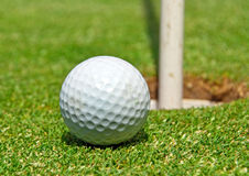 Golf ball at the hole. Ball view for the golf course with hole Stock Photos