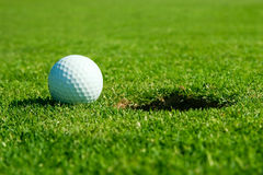 Golf ball and hole. Macro photo from golf ball and hole stock images