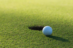 A golf ball and hole Royalty Free Stock Photos