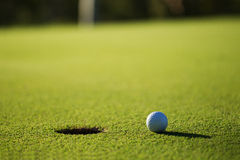 A golf ball and hole Stock Image