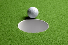 Golf ball at hole royalty free stock photography
