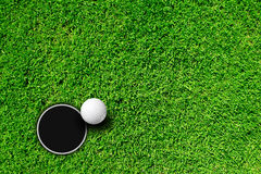 Golf ball and hole. Golf ball on putting green next to hole Royalty Free Stock Images