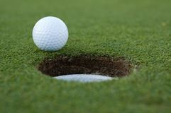 Golf ball and hole. Golf ball on putting green next to hole stock photography