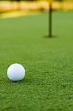 Golf ball and hole. Golf ball on putting green next to hole royalty free stock photos