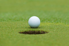 A golf ball and hole Royalty Free Stock Image