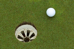 A golf ball and hole Stock Photos