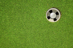 Golf ball in the hole. On green stock images