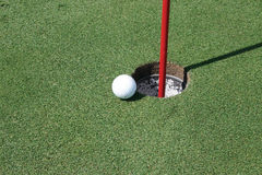 Golf Ball by the hole Stock Photography