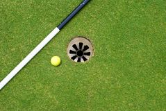Golf Ball at Hole. Yellow Golf Ball at Hole with Flag Pole Royalty Free Stock Image