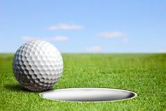 Golf ball at the hole Royalty Free Stock Photos