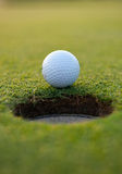 Golf ball by the hole Stock Photos
