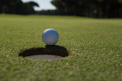 Golf ball in the hole Royalty Free Stock Image