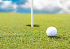 Golf ball at hole on field Royalty Free Stock Photography