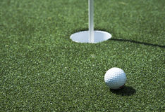 Golf ball and hole on a field. A golf ball sits near the hole on the putting green Royalty Free Stock Images