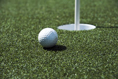 Golf ball and hole on a field Stock Image