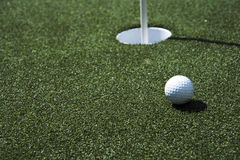 Golf ball and hole on a field Royalty Free Stock Photo