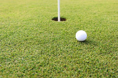 Golf ball at hole on grass Stock Image