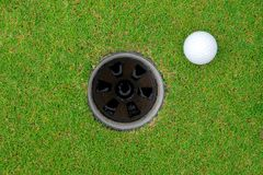 Golf ball and golf hole on green grass. stock photography