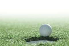 Golf ball and golf hole on green grass with copy space royalty free stock image