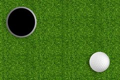 Golf ball and hole on the green grass royalty free stock image