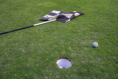 Golf Ball by Hole Marker Flagstick. On the putting green Stock Images