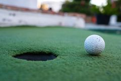 Golf ball and hole in a minigolf field royalty free stock photography
