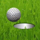 Golf ball and a hole Royalty Free Stock Photography