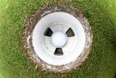 Golf Ball in the hole. A view of a golf ball in the cup taken with a fisheye lens royalty free stock images