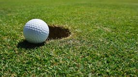 Golf ball by the hole stock image