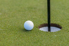 Golf ball and hole. White golf ball on a green close to hole stock photos