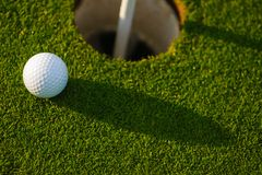 Golf ball inches from the cup Royalty Free Stock Photos