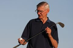 Golf Ball Inspection. Elderly golfer inspecting his golf ball and club Stock Photos
