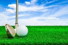 Golf ball and iron on artificial green grass Royalty Free Stock Photos