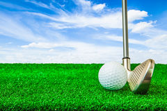Golf ball and iron on artificial green grass. And blue sky background stock photos