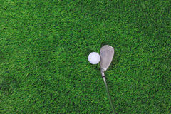 Golf ball and iron club on grass Royalty Free Stock Images