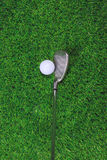 Golf ball and iron club on grass Stock Images