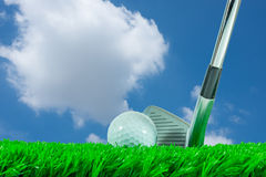 Golf ball and iron club. White golf ball and iron club on green artificial grass in blue sky background Royalty Free Stock Photos