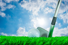 Golf ball and iron club. White golf ball and iron club on green artificial grass and shiny summer sky Royalty Free Stock Photos