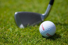 Golf Ball and Iron. A golf ball on the grass with iron stock image
