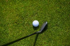 Golf Ball and Iron. A golf ball on the grass with iron stock photo