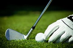 Golf ball, iron and hand on course Stock Images