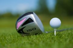 Golf Ball and Iron or putting. A golf ball on the tee on the grass with iron or putting royalty free stock image