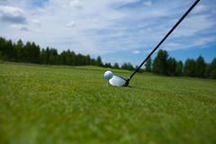 Golf Ball and Iron. A golf ball rests on the grass with iron royalty free stock photo