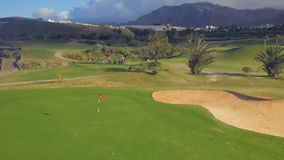 Golf ball lands close to the hole and flag. Aeriel view of a golf course Tenerife stock video footage