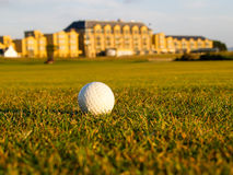 Golf ball lies in fairway. Golf ball in fairway of the Royal and Ancient Golf St Andrews Golf Course with resort and spa hotel in distant background Royalty Free Stock Photo
