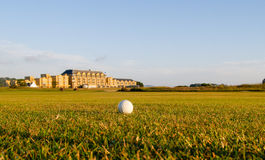 Golf ball lies in fairway. Golf ball in fairway of the Royal and Ancient Golf St Andrews Golf Course with resort and spa hotel in distant background Royalty Free Stock Photos