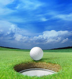 Golf ball on lip. Of cup of lovely beautiful golf course Stock Images