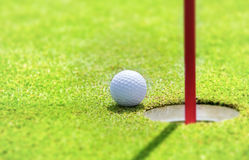 Golf ball. On lip of cup Royalty Free Stock Photography