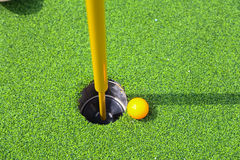 Golf ball on lip of cup. Stock Photo